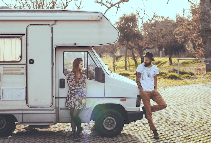 man and woman standing next to a camper